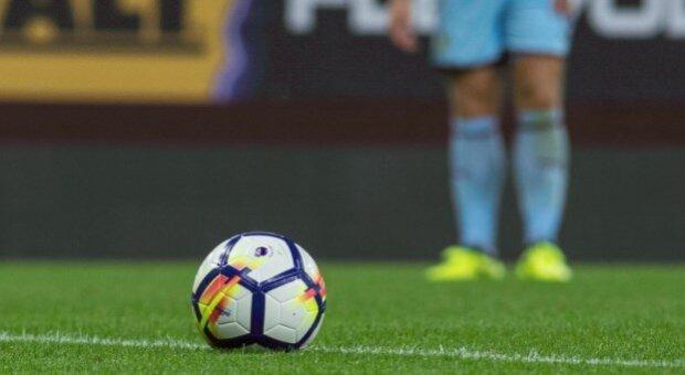 Balón de fútbol y jugador a punto de chutar